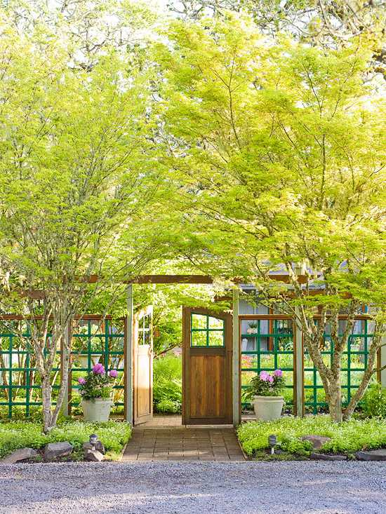 A windowed gate adds a sense of privacy, while still lending an airy feeling to the front yard. Via Better Homes & Gardens