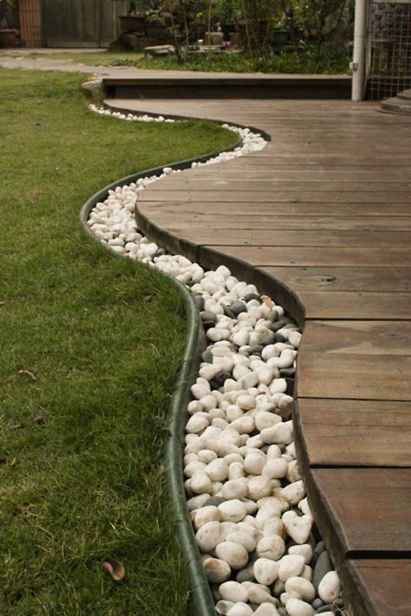 Use rocks to create garden edging along the edge of a timber decking pathway. The use of just a few dark grey rocks among the white is striking. Via Architecture and Design