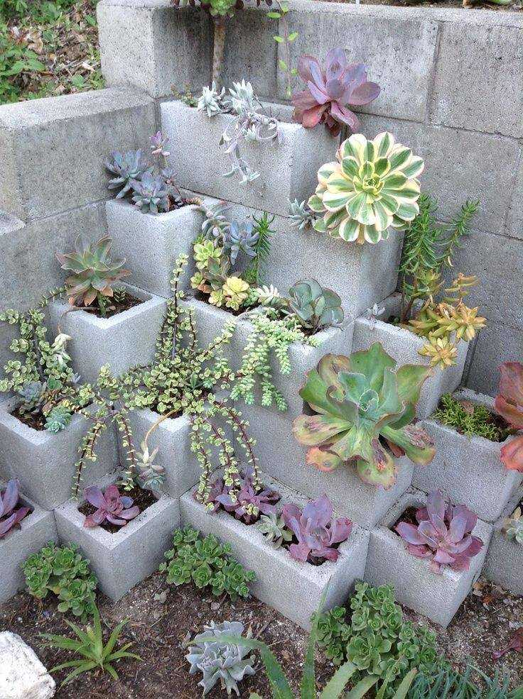 Create a garden feature using staggered cinder blocks as small pots. Via Slip Talk