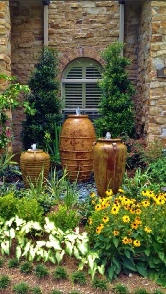 Ornate pots set into the garden create a beautiful haven for relaxation. Via Designs by Elizabeth